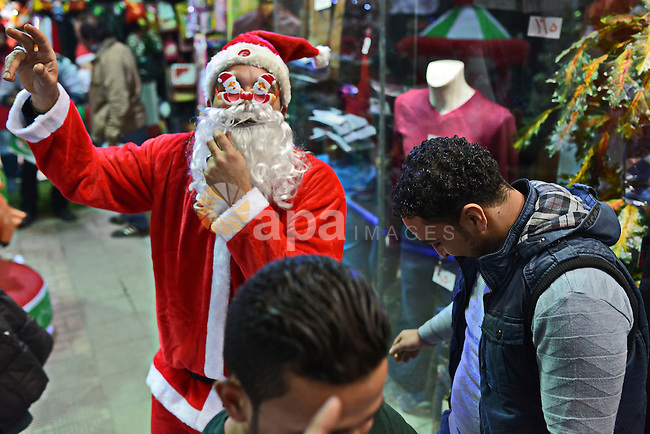 An Egyptian man in Santa Claus costume plays with children as part of Christmas and New Year festivities, in Cairo on December 31, 2014. Photo by Amr Sayed