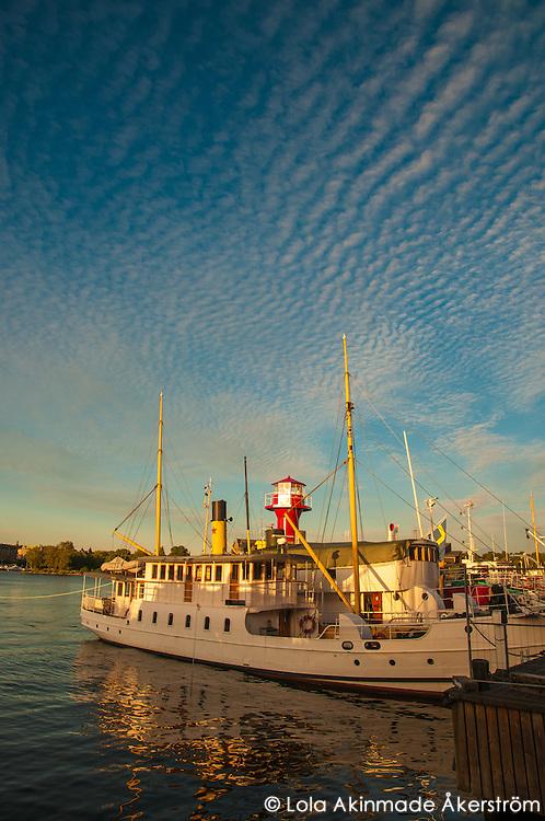 Golden sunlight reflecting off docked boats by Skeppsholmen.