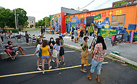 Residents watch Saturday, June 20, 2020, as Art Ventures artists complete a mural during the Fayetteville in Living Color event in the parking lot of St. Paul's Episcopal Church in Fayetteville. The event was held to register residents to vote, to support the Black Lives Matter movement and to foster community unity. Visit nwaonline.com/200621Daily/ for today's photo gallery.<br /> (NWA Democrat-Gazette/Andy Shupe)