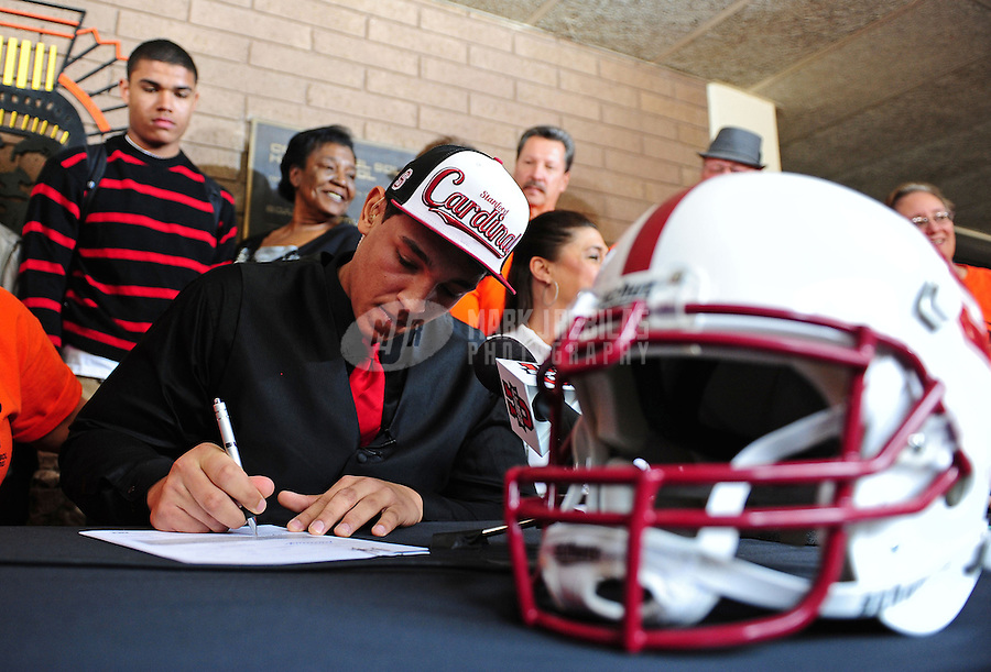 Feb. 1, 2012; Tempe AZ, USA; Corona del Sol Aztecs offensive lineman Andrus Peat signs paperwork a press conference at Corona del Sol High School to commit to play college football for the Stanford Cardinal. Mandatory Credit: Mark J. Rebilas-