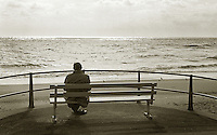 Man sitting on a bench looking out to sea.