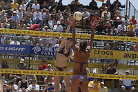 Huntington Beach, CA - 5/5/07:   Kerri Walsh spikes the ball over Logan Tom during May-Treanor / Walsh's 21-13, 21-12 victory over McPeak / Tom Saturday during the 2007 AVP CROCS Tour in Huntington Beach..Photo by Carlos Delgado / Special to AVP.com