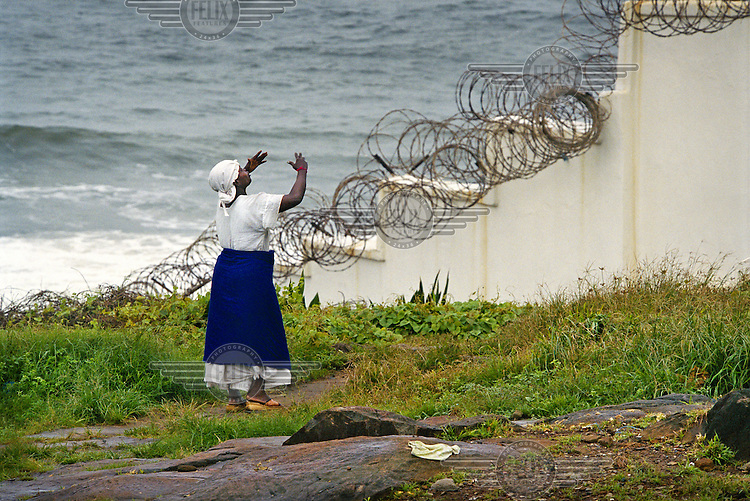 A woman, one of several hundred thousand displaced people living in central Monrovia, pleads for intervention outside the wall of the fortified US compound, Mamba Point..The ongoing conflict in Libera intensified in March 2003 when rebels opposed to the government of Charles Taylor gained territory across much of the country, advancing on the capital city Monrovia. In August 2003 Taylor agreed to hand over power to an interim government and went into exile, which led to the signing of a peace agreement. Charles Taylor was indicted for war crimes by a UN court, and is accused of fuelling conflict across West Africa.