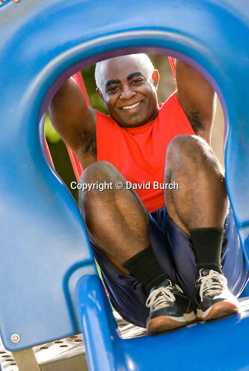 Man playing on slide, portrait, smiling
