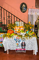 Oaxaca, Mexico, North America.  Day of the Dead Celebrations.  Family Altar in Living Room in Memory of Past Ancestors.  Flowers, Marigolds, Candles, Fruit, Photos.