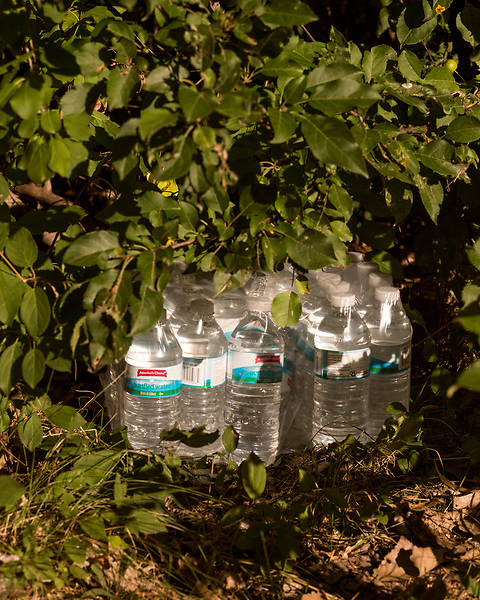 August 7, 2016. Flint, Michigan.<br /> A case of bottled water is hidden in the bushes along the Flint River. Although Flint city government says the water is safe to drink when filtered properly, many residents still rely on bottled water for drinking and bathing. Through federal emergency funds, the state distributes 1000's of cases of bottled water nearly every day to Flint residents.<br />  In April 2014, the city of Flint switched its water source from the Detroit Water and Sewerage Department to using the Flint River in an effort to save money. When the switch occurred, the city failed to have corrosion control treatment in place for the new water. This brought about a leaching of lead from pipes into the water, increasing the lead content in the drinking water to levels far above legal limits. After independent sources brought this to light, the city admitted the water was unsafe and legal battles have ensued between resident and the local and state governments.