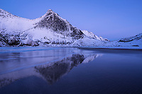 Reflection of steep snow covered granite cliffs of Helvetestind mountain peak on Bunes beach, Moskenesøy, Lofoten Islands, Norway