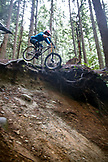 CANADA, Vancouver, British Columbia, mountain biker Andrew Baker gets air on a trail in the rainforest, North Vancouver