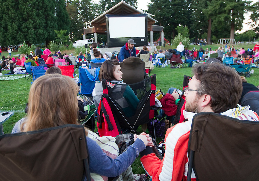 Robin Schwartz (L) and Nathan Klavano hold hands as they watch a movie in Marshall Park in Vancouver Friday July 15, 2016. A star wars movie was shown on the lawn following a Seahawks event. (Photo by Natalie Behring/ for the The Columbian)