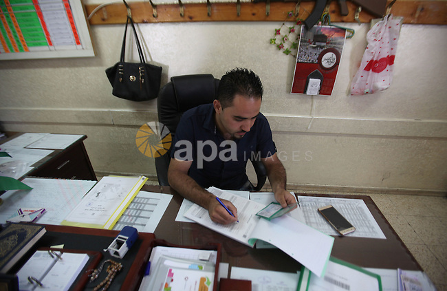 A Palestinian from Central Elections Commission (CEO) works at Voter registration centers in the West Bank city of Nablus on July 24, 2016. The Palestinian Central Elections Commission (CEO) announced Saturday that voter registration centers would be open from Saturday until Wednesday in all local and municipal councils across the occupied West Bank and Gaza Strip in preparations for the upcoming local elections in October. Photo by Nedal Eshtayah