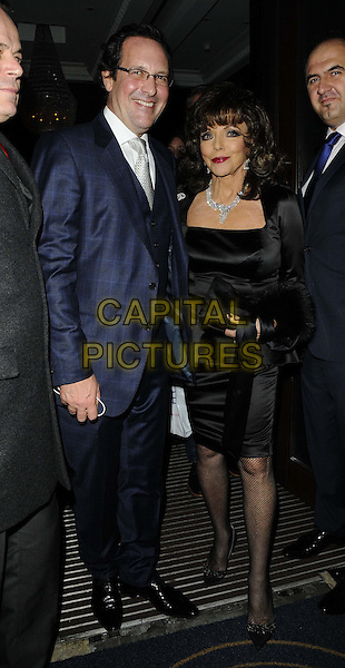 Percy Gibson &amp; Joan Collins<br /> attended the &quot;Joan Collins: Passion for Life&quot; book launch party, The Westbury Hotel, London, England.<br /> October 21st, 2013<br /> full length black silk satin peplum dress blue suit glasses married husband wife <br /> CAP/CAN<br /> &copy;Can Nguyen/Capital Pictures