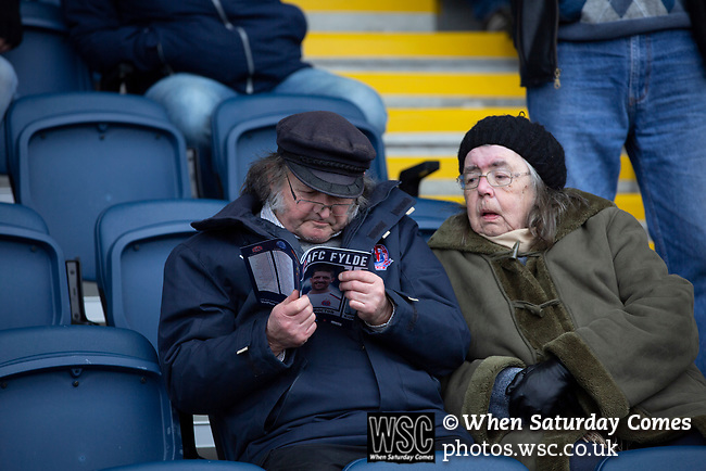 AFC Fylde 1, Aldershot Town 0, 14/03/2020. Mill Farm, National League. Two elderly home supporters reading the match programme in the main stand before AFC Fylde took on Aldershot Town in a National League game at Mill Farm, Wesham. The fixture was played against the backdrop of the total postponement of all Premier League and EFL football matches due to the the coronavirus outbreak. The home team won the match 1-0 with first-half goal by Danny Philliskirk watched by a crowd of 1668. Photo by Colin McPherson.