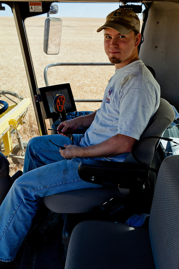A farmer sits in the cab of a Case 8120 combine.