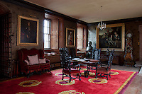 A set of heavily carved chairs surround table in a room clad with embossed leather, patterned with the family coat of arms