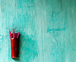 Incense 05 - Red incense stick holder on a blue wall in Nguyen Thai Hoc St, Hoi An, Viet Nam