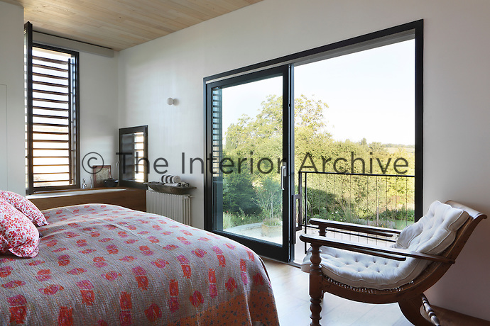 A simple bedroom, with large sliding glass doors to see the countryside whilst relaxing in bed