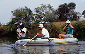 Mbati, Zambia. Tourists in an Avon rubber dingy boat on Lake Tanganyika, using binoculars, with guide.
