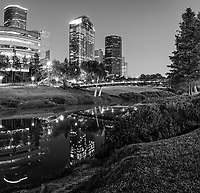 Houston- Sabine-Promenade -Skyline-Pano-BW-  This is a vertical black and white panorama of the Sabine to Bagby promenade over the Buffalo Bayou with the Houston Skyline at the blue hour. You can see the Wells Fargo building towering as the second tallest building in the city along with the impressive Heritage Plaza as the fifth tallest in the city. We capture a pano image so we could capture the Houston skyline and bridge along with their reflections in the waters of the Buffalo Bayou in downtown Houston.
