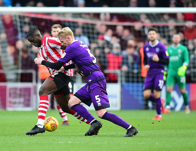 Lincoln City's John Akinde shields the ball from Grimsby Town's Ludvig Ohman<br /> <br /> Photographer Andrew Vaughan/CameraSport<br /> <br /> The EFL Sky Bet League Two - Lincoln City v Grimsby Town - Saturday 19 January 2019 - Sincil Bank - Lincoln<br /> <br /> World Copyright &copy; 2019 CameraSport. All rights reserved. 43 Linden Ave. Countesthorpe. Leicester. England. LE8 5PG - Tel: +44 (0) 116 277 4147 - admin@camerasport.com - www.camerasport.com
