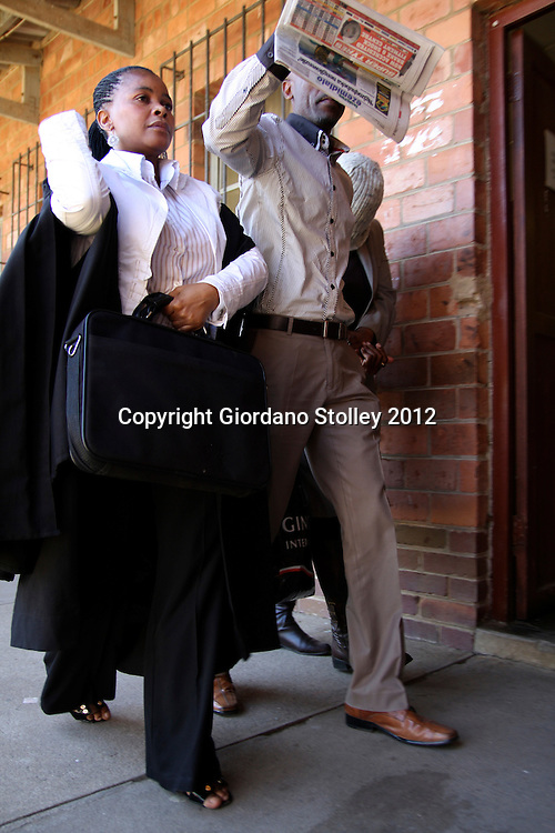 DURBAN - 13 August 2012 - Lawyer Nomfanelo Mgulwa (left) and an unknown man shield Annette Mfeka, whose covered head can be seen on the right from the media photographers at the Ntuzuma Magistrate's Court. Mfeka, an education department employee, was charged with corruption and and trying to extort money from a teacher..Picture: Giordano Stolley/Allied Picture Press/APP