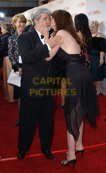 GEORGE LUCAS & MACKENZIE PHILLIPS.The 33rd AFI Life Achievement Award: A Tribute to George Lucas held at The Kodak Theatre in Hollywood, California  .June 9th, 2005.full length black tuzedo black sheer dress kiss gesture.www.capitalpictures.com.sales@capitalpictures.com.Supplied By Capital PIctures