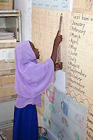 Jambiani, Zanzibar, Tanzania.  African Muslim Schoolgirl Reciting Numbers on a Wall Chart.