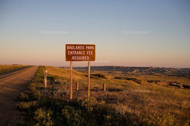 "A sign reading ""Badlands Park Entrance Fee Required"" stands next to a dirt road at the edge of Badlands National Park in South Dakota, USA."