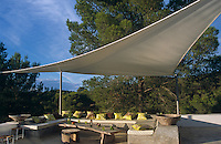 A sail-like awning provides shade over a built-in concrete banquette that forms the seating area beside the swimming pool