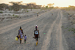 KENYA Turkana, Lodwar, Turkana land, dusty sand road during dawn, family walking with jerry cans to fetch water