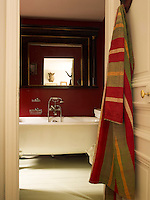 The red-painted bathroom, adjoins the master bedroom, a striped bath robe hanging on the back of the door