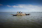 Fishers at work on a boat in the Brahmaputra River near the island village of Kunderpara in northern Bangladesh.