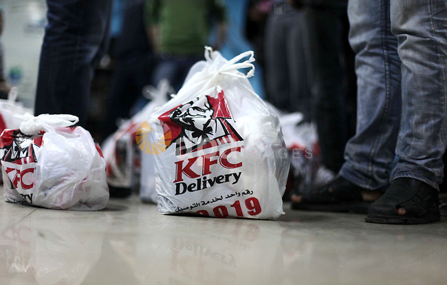 "Delivery employees organize bags of food from Kentucky Fried Chicken after it arrived in Gaza City through an underground tunnel linking the Gaza Strip to Egypt, on May 16, 2013. Fast food is just the latest trend for smugglers seeking to turn a buck by bringing in hard-to-get products to the Gaza Strip, which has been under an Israeli blockade since 2007. It's not exactly ""fast"" -- taking several hours to arrive, with the Palestinian delivery company behind it charging hefty prices to cover the cost of fuel and transport. Photo by Ashraf Amra"