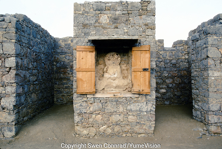 Sculpture of Buddha under protection in a monastery in the Swat valley. .Taxila, the main centre of Gandhara, is over 3,000 years old. Taxila had attracted Alexander the great from Macedonia in 326 BC, with whom the influence of Greek culture came to this part of the world. Taxila later came under the Mauryan dynasty and reached a remarkable matured level of development under the great Ashoka. During the year 2 BC, Buddhism was adopted as the state religion, which flourished and prevailed for over 1,000 years, until the year 10 AD. During this time Taxila, Swat and Charsadda (old Pushkalavati) became three important centers for culture, trade and learning. Hundreds of monasteries and stupas were built together with Greek and Kushan towns such as Sirkap and Sirsukh, both in Taxila.