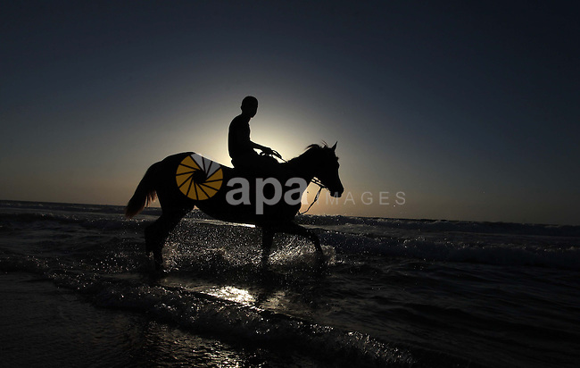 A Palestinian man rides a horse on a beach in Gaza City May 2, 2014. Photo by Ashraf Amra