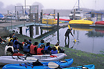 Instructor teaching class of students to kayak, Morro Bay State Park harbor, California