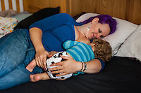 A young woman breastfeeds her toddler off to sleep whilst lying on her bed.<br /> <br /> 27/09/12<br /> Berkshire, England, UK