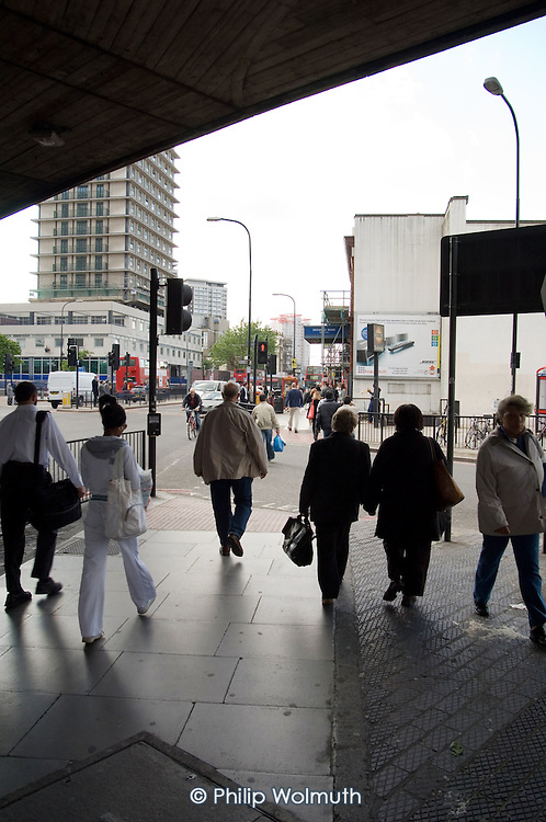 Pedestrians walk beneath the Westway flyover on the Edgware Road, London.