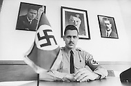 February 10, 1972, Arlington, Virginia. Matt Koehl, the comander of the White National Socialist Party at his desk, On the left a picture of Rockwell, the founder of their Party, and above his head a portrait of Adolf Hitler, and a portrait of himself on the right side of the picture.