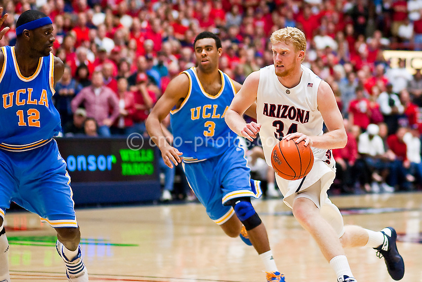 Feb 14, 2009; Tucson, AZ, USA; Arizona Wildcats forward Chase Budinger (34) tries to dribble away from UCLA Bruins guard/forward Josh Shipp (3) and center Alfred Aboya (12) in the second half of a game at the McKale Center.   The Wildcats won the game 84-72 to break an eight-game losing streak against the Bruins and win their seventh game in a row.