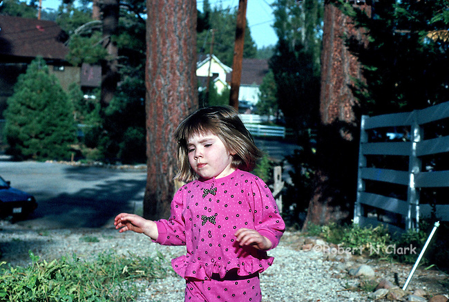 Girl walking in yard with concentrated look on her face, in mountain settting