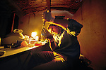 By the light of a Kerosene lamp, Jason Blue-Smith of the National Geographic Genographic Project, extracts DNA from blood samples, using a generator-powered centrifuge. Faya-Largeau, Chad.