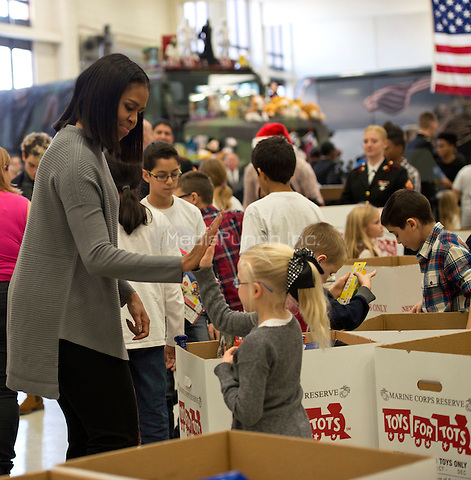 Washington, DC,December 7, 2016, USA:  First Lady Michelle Obama visits Joint Base Anacostia-Bolling  where she helps with the distribution of toy and gifts donated by the executive office of the presidential staff to the Marine Corps Reserver Toys for Tots program. Obama gives a high five to one of her helpers. Patsy Lynch/MediaPunch