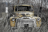 Old, yellow, abandoned GMC truck.
