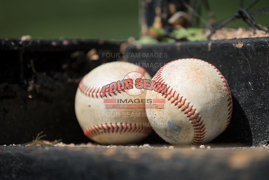 Two Rawlings baseballs sit on the top step of the Kannapolis Intimidators dugout prior to the game against the Greensboro Grasshoppers at Kannapolis Intimidators Stadium on August 13, 2017 in Kannapolis, North Carolina.  The Grasshoppers defeated the Intimidators 4-1 in 10 innings in the completion of a game suspended on August 12, 2017.  (Brian Westerholt/Four Seam Images)