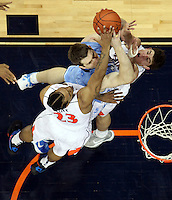 North Carolina Tar Heels forward Tyler Zeller (44) is defended by Virginia Cavaliers forward Mike Scott (23) and Virginia Cavaliers guard Joe Harris (12) during the game in Charlottesville, Va. North Carolina defeated Virginia 54-51.