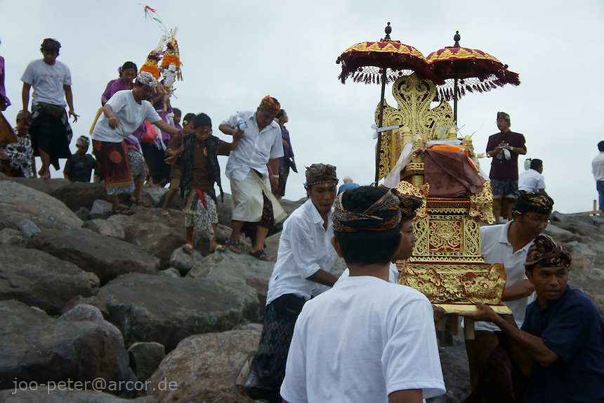 family members carfully carry golden throne with ashes of the passed family member down the rocks next to the beach, to hand over all to the sea,  cremation ceremonies,  September 17th 2011,  Bali, archipelago Indonesia. Cremation ceremonies in Bali guide the spirit of the passed family member from underworld death realms to divine heavenly nature spirit life circle uprise of the death, becoming a divine ancestor to be reborn in the next generation of the family