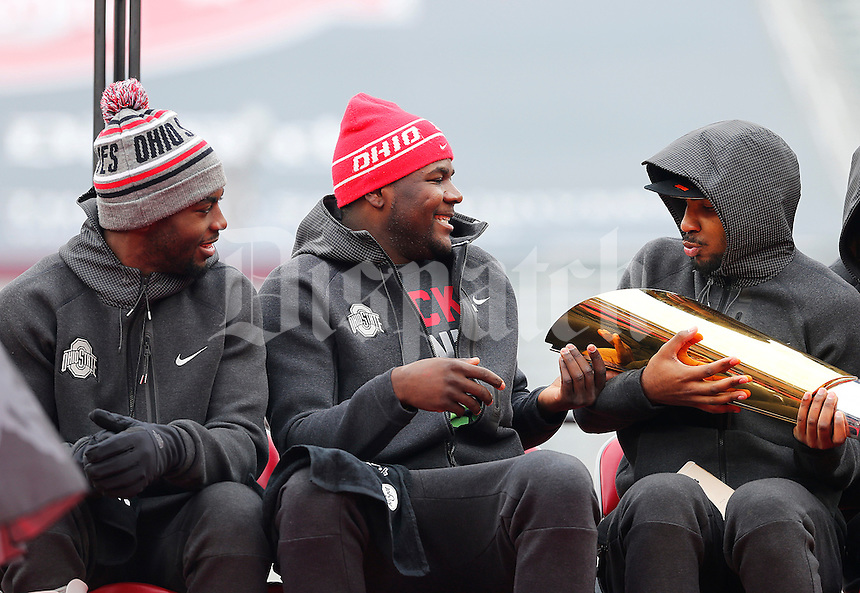 Quarterback Cardale Jones, center, hands off the trophy to quarterback Braxton Miller, right, as quarterback J.T. Barrett, left, watches during the Ohio State Football National Championship Celebration at Ohio Stadium, Saturday morning, January 24, 2015. More than 40 thousand fans packed the lower stands in the stadium to celebrate the National Championship win with the football team. (The Columbus Dispatch / Eamon Queeney)