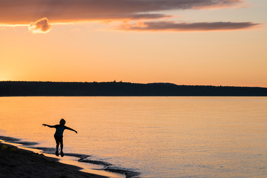 Enjoying an empty Lake Superior beach at dusk at Little Presque Isle natural area near Marquette, Michigan.