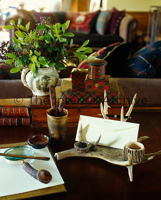 On the writing desk in the drawing room is an ink stand made of antler horn and a pile of tartan boxes