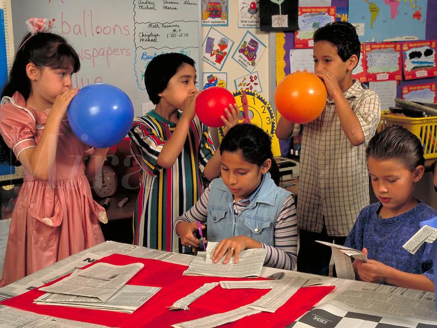 HISPANIC ELEMENTARY SCHOOL CHILDREN MAKE A PiNATA IN CLASS FOR FIESTA PARTY. ELEMENTARY SCHOOL CHILDREN. SAN ANTONIO TEXAS.
